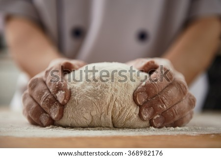 Woman chef with raw dough. Young female in uniform preparing bread dough on wooden table.