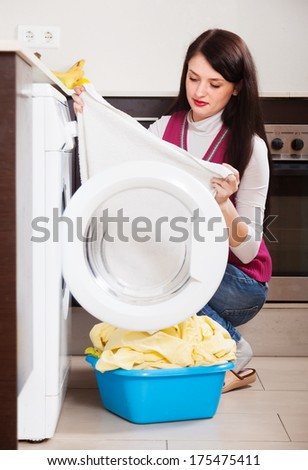 woman cheking white clothes near washing machine  at home