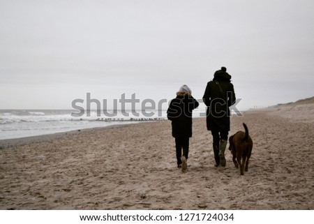 Woman, child and brown Labrador Retriever dog walking at the beach in winter with sea in background #1271724034
