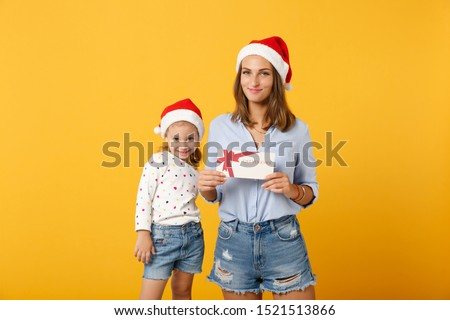 Woman child baby girl in Christmas Santa hat hold certificate. Mommy little daughter isolated on yellow background studio portrait. Happy New Year 2020 celebration holiday concept. Mock up copy space