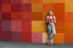 Woman choose music to listen on smartphone during jogging in city, copy space, colorful background