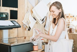 Woman chooses and buys products in zero waste shop. Weighing dry goods in plastic free grocery store. Girl with cotton reusable net mesh bag weigh glass jars on scales. Eco shopping at local business