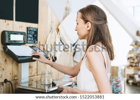 Woman chooses and buys products in zero waste shop. Weighing dry goods in plastic free grocery store. Girl with cotton reusable bag weigh glass jars on scales. Eco shopping at local business #1522053881