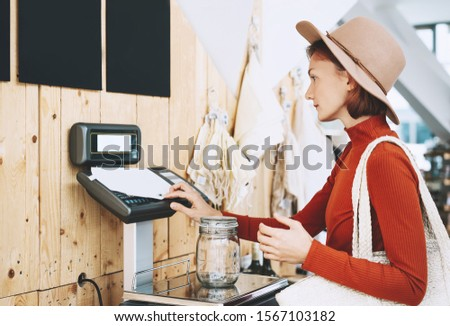 Woman chooses and buys products in zero waste shop. Weighing dry goods in plastic free grocery store. Girl with cotton reusable bag weigh glass jars on scales. Eco shopping at local business #1567103182