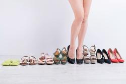 Woman chooses classic black heeled shoes.