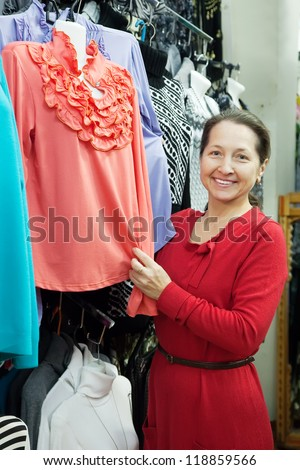 Woman  chooses clothes at fashionable shop