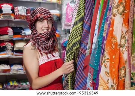 woman  chooses  egyptian shawl at  shop