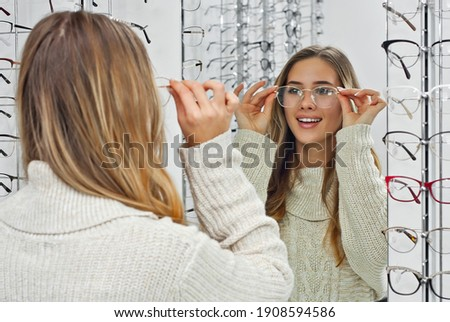 Woman chooses glasses in the store. Blonde in a beige sweater measures glasses near the mirror. Girl on a background of shop windows with different models of glasses. Foto stock ©