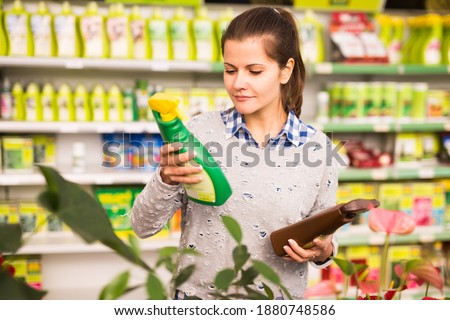Woman chooses sprayer with insecticides in store. High quality photo Foto stock ©