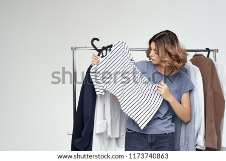 woman chooses things on her shoulders in the dressing room                     #1173740863