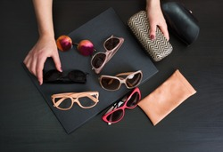 Woman choosing a pair of stylish sunglasses