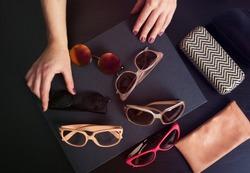 Woman choosing a pair of stylish sunglasses. Toned image
