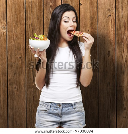 woman choosing a slice of pizza instead of a salad against a wooden background