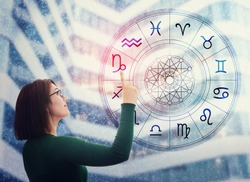 Woman choosing a zodiac sign from the astrological wheel to find the future predictions. Having trust in horoscope, consulting stars and believe in the power of universe. Astrology esoteric concept.