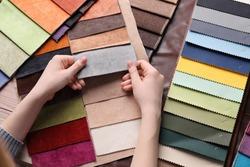 Woman choosing among colorful fabric samples, closeup