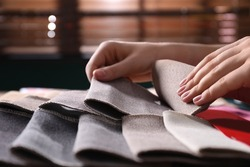 Woman choosing among different fabric samples indoors, closeup