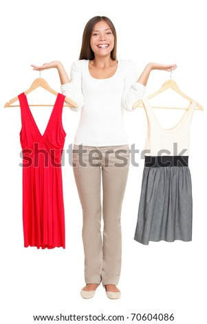Woman choosing between dresses and can not make decision. Beautiful Asian / Caucasian woman showing clothes isolated on white background in full figure.