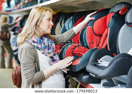 woman choosing child car seat for newborn baby in shop supermarket