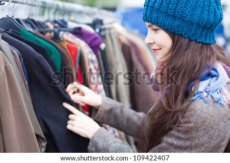 Woman choosing clothes at flea market