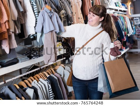 Woman choosing clothes for baby in children`s cloths shop