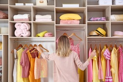 Woman choosing clothes from large wardrobe closet
