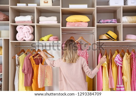 Woman choosing clothes from large wardrobe closet #1293384709