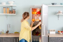 Woman choosing food in modern fridge at home