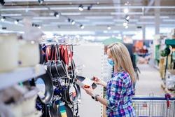 Woman choosing frying pan in supermarket. Shopping during lock down.