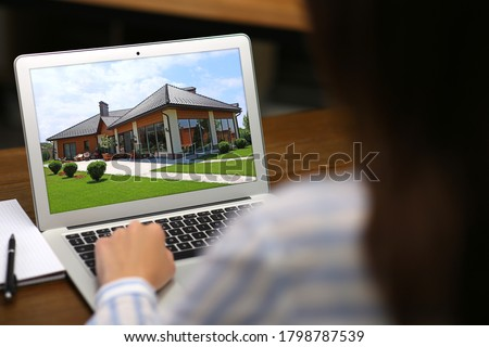 Woman choosing new house online using laptop or real estate agent working at table, closeup Stockfoto ©