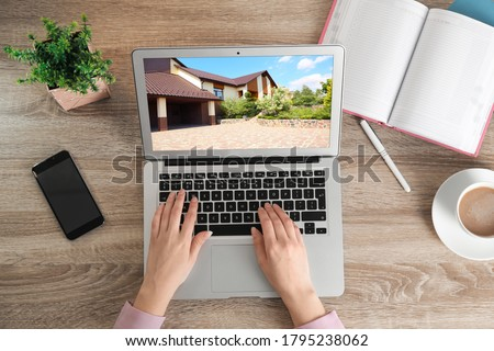 Woman choosing new house online using laptop or real estate agent working at table, top view Stockfoto ©