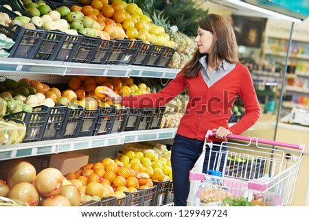 woman choosing orange or mandarin during shopping at fruit vegetable supermarket
