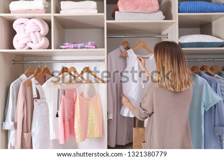 Woman choosing outfit from large wardrobe closet with stylish clothes and home stuff #1321380779