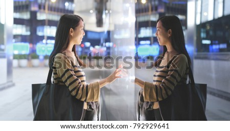 Woman choosing product inside shop window in the city at night with window reflection