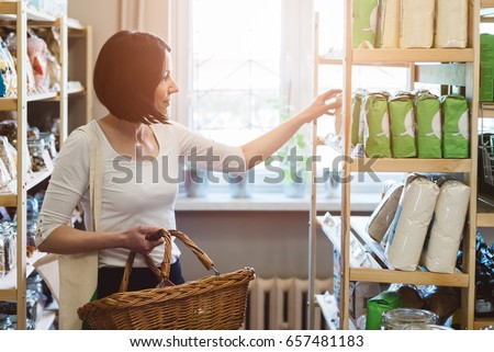 Woman choosing products in ecological shop with healthy food