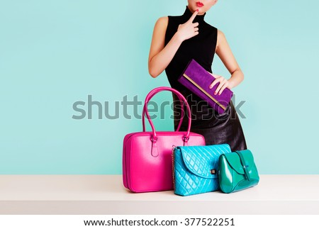 Woman choosing the bag from many colorful bags.Isolated on light blue background. Shopping addiction.  #377522251