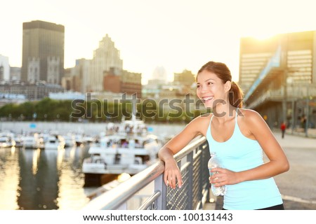 Woman city runner resting after running workout. Female fitness model smiling happy drinking water enjoying a break. Beautiful fit mixed race Asian Chinese and Caucasian woman outdoors.