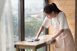 woman cleaner cleaning, disinfecting with disinfectant living room in apartment. portrait of asian woman cleaning staff doing housekeeping or domestic helper job. young adult asian woman model