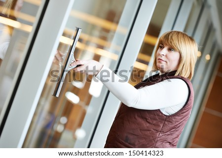 woman cleaner worker in uniform cleaning indoor window of business building - stock photo
