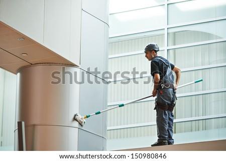 woman cleaner worker in uniform cleaning indoor window of business building