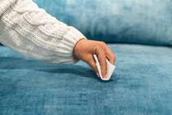 Woman cleaning a blue sofa with white cloth. Sofa cleaning. Removing stains.