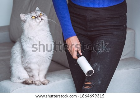 Photo of  Woman cleaning clothes with clothes roller, lint roller or sticky roller from cats hair. Cats hair on clothes. Cleaning hair from pets