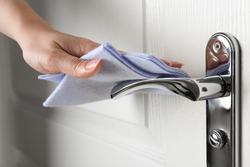 Woman cleaning door handle with rag indoors, closeup
