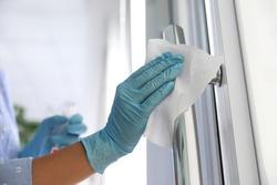 Woman cleaning door handle with wet wipe indoors, closeup