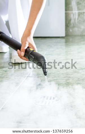 Woman cleaning  drain in bathroom with a lot of steam