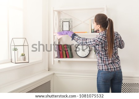 Woman cleaning dust from bookshelf. Young girl sweeping shelf, spring cleaning concept, copy space #1081075532