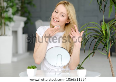 Woman Cleaning Face With White Pad. Beautiful Girl Removing Makeup White Cosmetic Cotton Pad. Happy Smiling Female Taking Off Makeup From Facial Skin With Cosmetic Pad. Face Skin Care. Home interior
