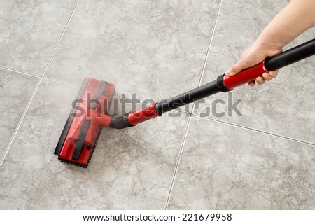 woman cleaning floor steam cleaning into the room