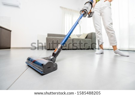 Woman cleaning floor with cordless vacuum cleaner in the modern white living room. Concept of easy cleaning with a wireless vacuum cleaner