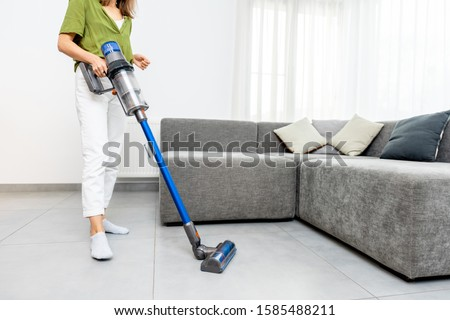 Woman cleaning floor with cordless vacuum cleaner in the modern white living room. Concept of easy cleaning with a wireless vacuum cleaner Stockfoto ©