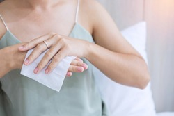 Woman cleaning hands by wet wipes tissue and alcohol disinfectant on bed during wake up at home, protection coronavirus (Covid-19) infection. Lifestyle, New Normal and Clean surface concept